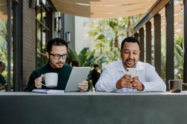Men working with digital devices in a cafe