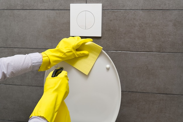 Men in yellow gloves cleaning toilet bowl. home cleaning concept.