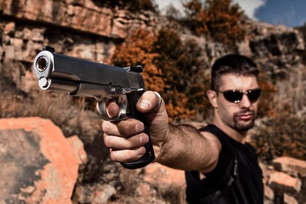 위협적인 남자는 권총을 가리키는