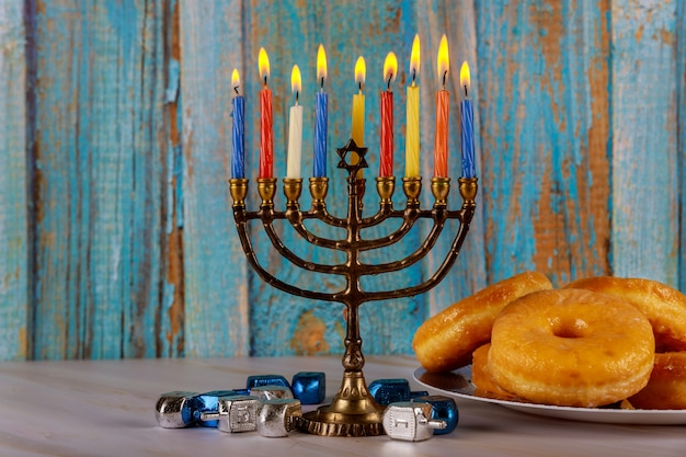 Menorah, donuts and dreidels on table hanukkah concept.