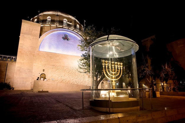Menorah - the golden seven-barrel lamp - the national and religious jewish emblem near the dung gates on the background of the synagogue hurva at night in the old city of jerusalem, israel.