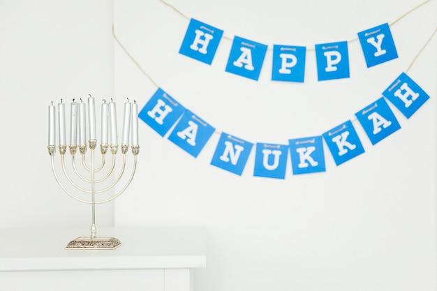 Menorah near happy hanukkah garland