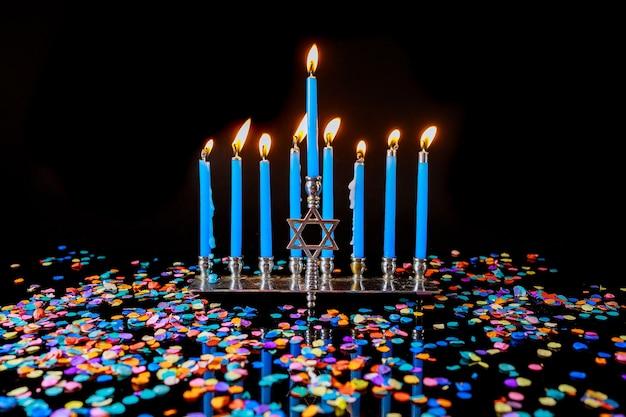 Менора с голубыми зажженными свечами и конфетти для еврейского праздника ханука.