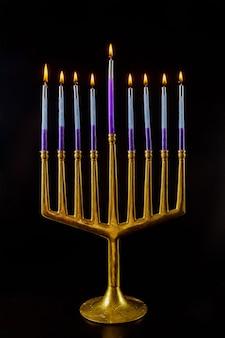 ユダヤ教の祝日祭でハヌカのために燃え尽きたろうそくと本枝の燭台