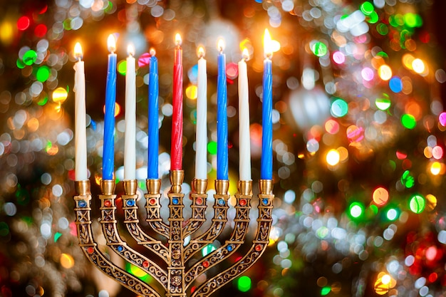 Менора с зажженными свечами для хануки на фоне блеска с расфокусированным огнями.