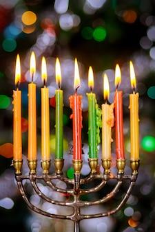 焦点がぼけたカラフルなライトでハヌカのために燃えるろうそくを持った本枝の燭台。ユダヤ教の祝日。