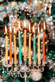 Menorah with burning candles for hanukkah on sparkle surface with blurred lines