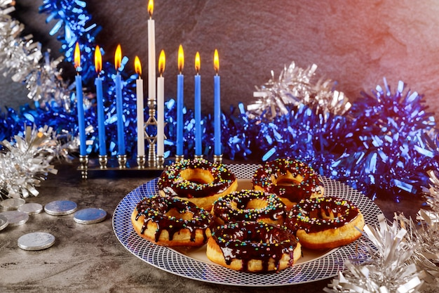 Menorah with burning candles and sweet donuts with chocolate and sprinkle on the top