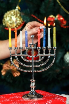Menorah with candles for hanukkah on the background of the new year tree