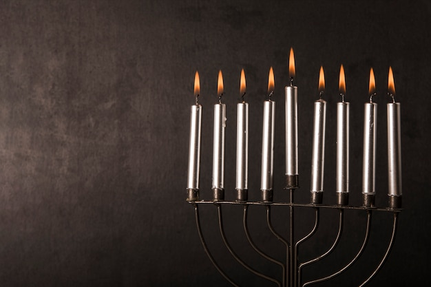 Menorah with candles near gray wall