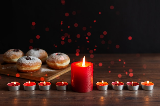 Menorah with candles (traditional candelabra) and traditional donuts sufganiyot on wooden table for hanukkah celebration.