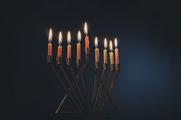 Menorah with colorful candles for hanukkah on light blue background, close up