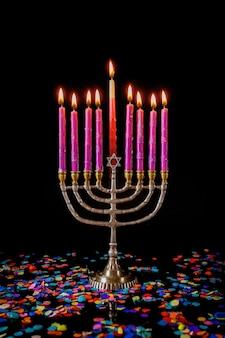 Менора с розовыми зажженными свечами и конфетти для еврейского праздника ханука.