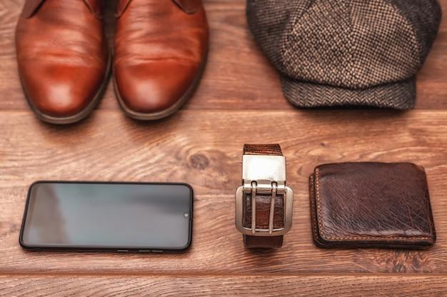Мужские аксессуары кожаная обувь пояс кошелек кепка и смартфон на деревянном фоне