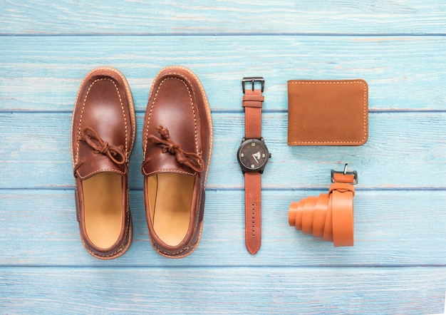 Mens accessory with loafer shoe, wallet leather, brown watch and belt  isolated on a blue wooden background. top view.