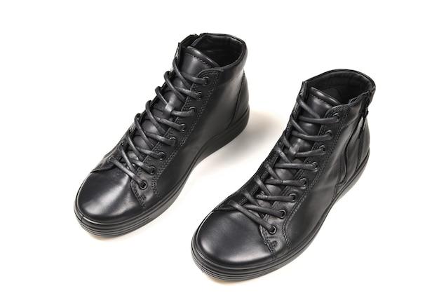 Мужские черные кожаные туфли и черный фотоаппарат на черном фоне
