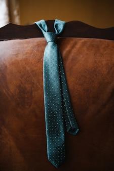 가죽 소파 뒷면에 흰색과 파란색 물방울 무늬가 있는 남성용 짙은 녹색 넥타이