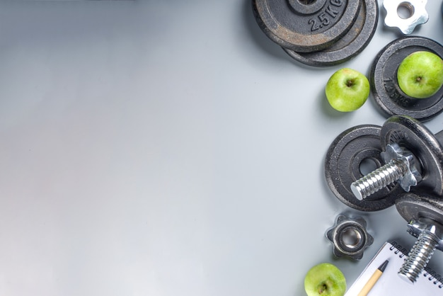 Предпосылка фитнеса людей с гантелями темного железа, кроссовками, наушниками, яблоками gren и бутылкой с водой. на сером фоне вид сверху копией пространства