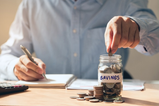 Mens hand holding coins putting in glass saving money and investing concept saving money for finance accounting
