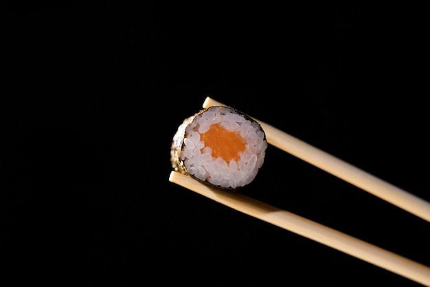 Mens hand holding wooden sticks california roll with salmon