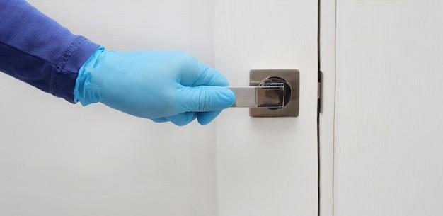 파란색 보호 장갑을 착용 한 남성은 문을 열거 나 닫습니다.