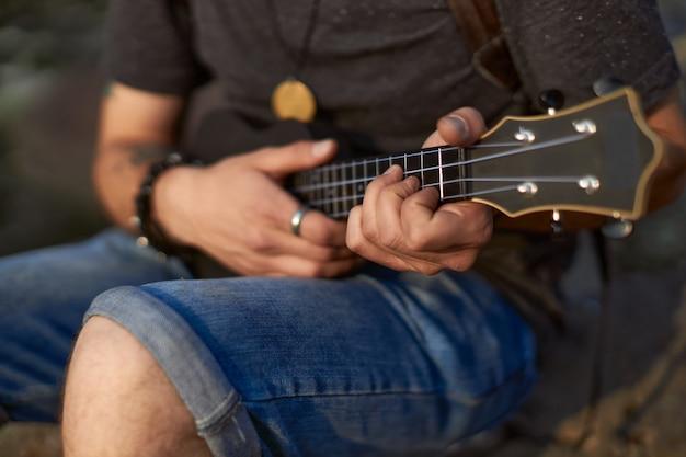 남자의 손은 손으로 현을 쥐고 있는 검은색 우쿨렐레를 연주합니다. 고품질 사진