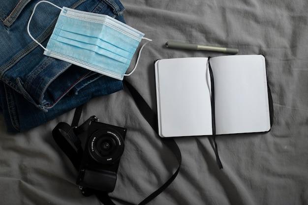 Мужские джинсы цифровой фотоаппарат цифровой фотоаппарат блокнот с местом для ручки и хирургической маски на серых простынях