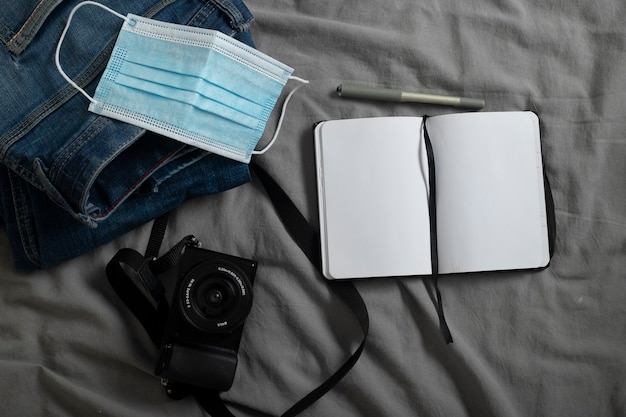 Mens jeans digital camera digital camera notepad with space for writing pen and surgical mask on gray sheets