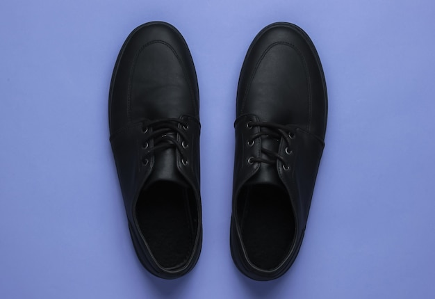 Mens leather black shoes on a purple background