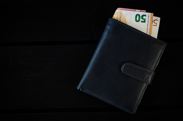 Mens leather wallet with euro, on black table
