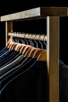 メンズシャツ、スーツはラックにぶら下がっています。ブティックでジャケットを着たハンガー。ラックにぶら下がっている男性用のスーツ。衣料品小売店のハンガーにぶら下がっているさまざまな色のメンズスーツ、クローズアップ。