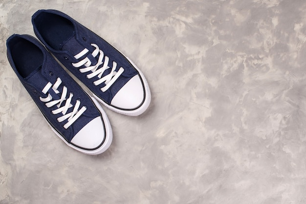 Mens sneakers in dark blue thick fabric, top view. hipster shoes on a modern concrete grey background.
