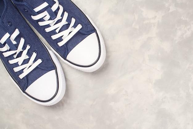 Мужские кроссовки из плотной ткани темно-синего цвета, вид сверху. битник обувь на современном бетонном сером фоне.
