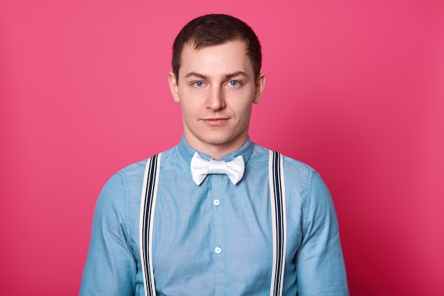 Mens style and fashion concept. handsome blue eyed man with dark hair, smooth skin, wears shirt, bowtie and suspenders, looks , redy for date with girlfriend, isolated on pink wall.