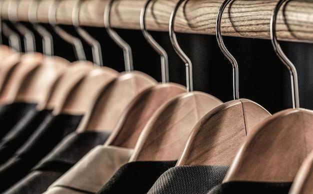 소매 옷가게, 클로즈업에서 옷걸이에 매달려 있는 다양한 색상의 남성용 정장. 망 셔츠, 옷걸이에 매달려 있습니다. 부티크에 재킷이 달린 옷걸이. 랙에 매달린 남성용 정장.