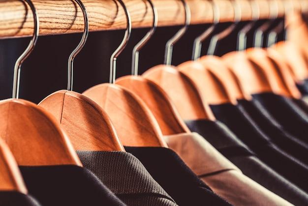 衣料品店のハンガーにぶら下がっているさまざまな色のメンズスーツ、クローズアップ。メンズシャツ、スーツはラックにぶら下がっています。