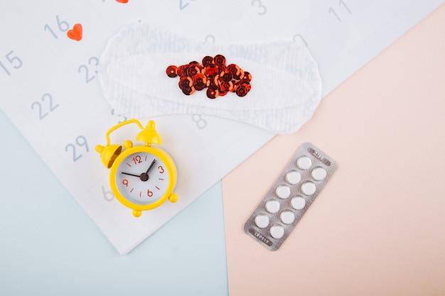 패드, 알람 시계 및 피임약이있는 생리 달력. 월경 기간 개념. 생리통에 대한 진통제.
