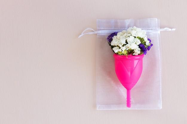 月経カップと花のつぼみがクローズアップ