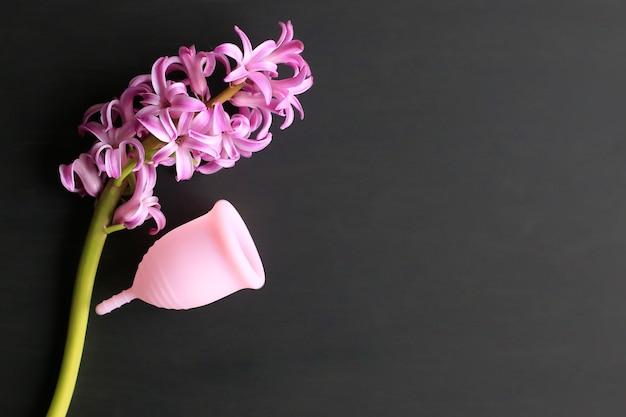 黒の背景に月経カップとヒヤシンスの花