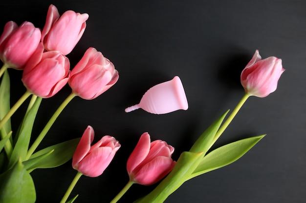 黒の背景に月経カップとピンクのチューリップ。女性の健康。