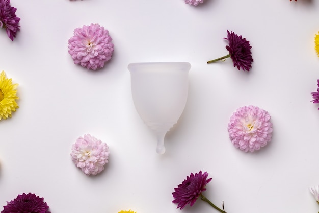 Menstrual cup on floral pattern background top view, copy space