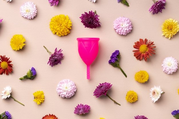 Menstrual cup on floral pattern top view