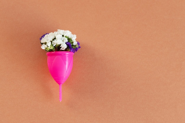 Menstrual cup and flower bud close up photo