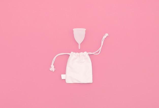 親密な衛生のための月経カップ、カップを保管するためのリネンバッグ。コピースペースとピンクの背景。