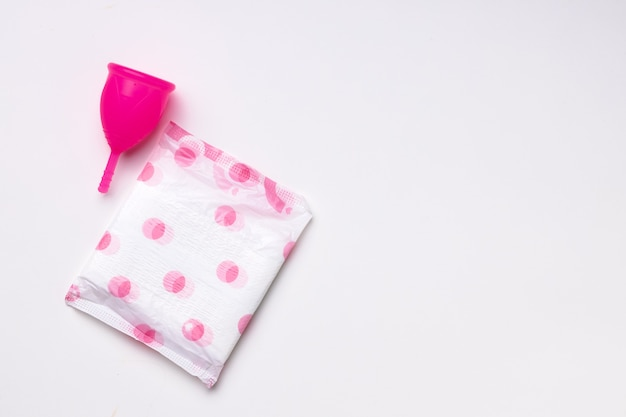 Menstrual cup and hygienic pad on paper background