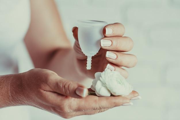 Менструальная чаша в женских руках. женщина держит цветок и силиконовую гигиеническую чашку, новое устройство для минимизации отходов и защиты окружающей среды.