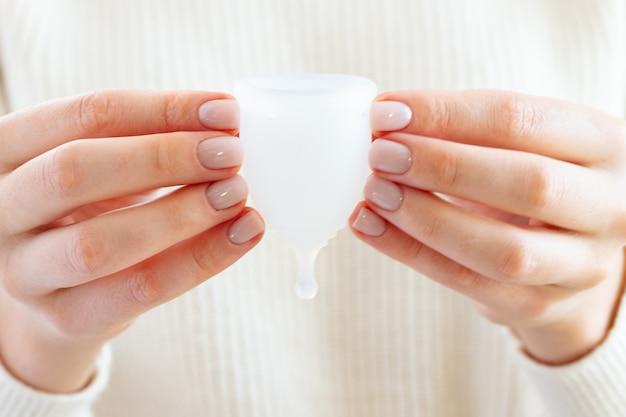女性の手に月経カップのクローズアップ写真