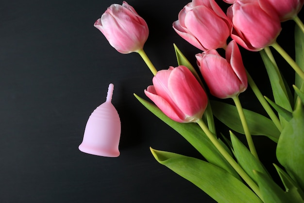 Menstrual cup and pink tulips on a black background.