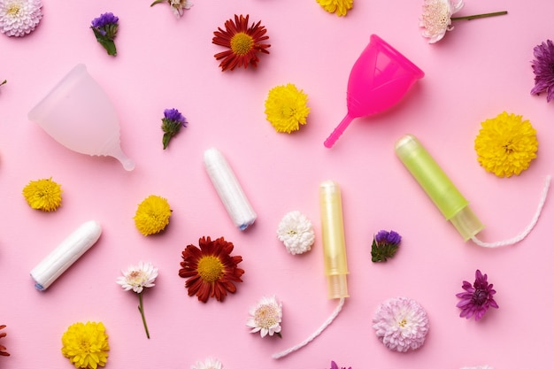 Menstrual cup and tampons on floral pattern background top view