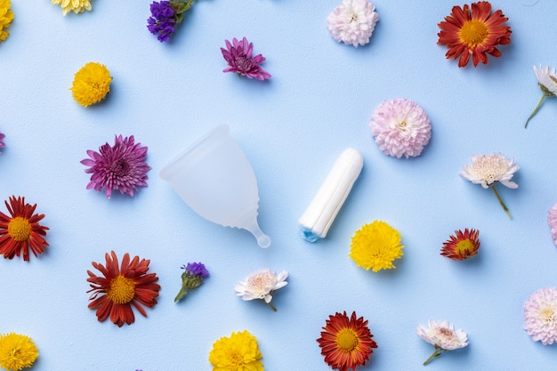 Menstrual cup and tampons on floral pattern